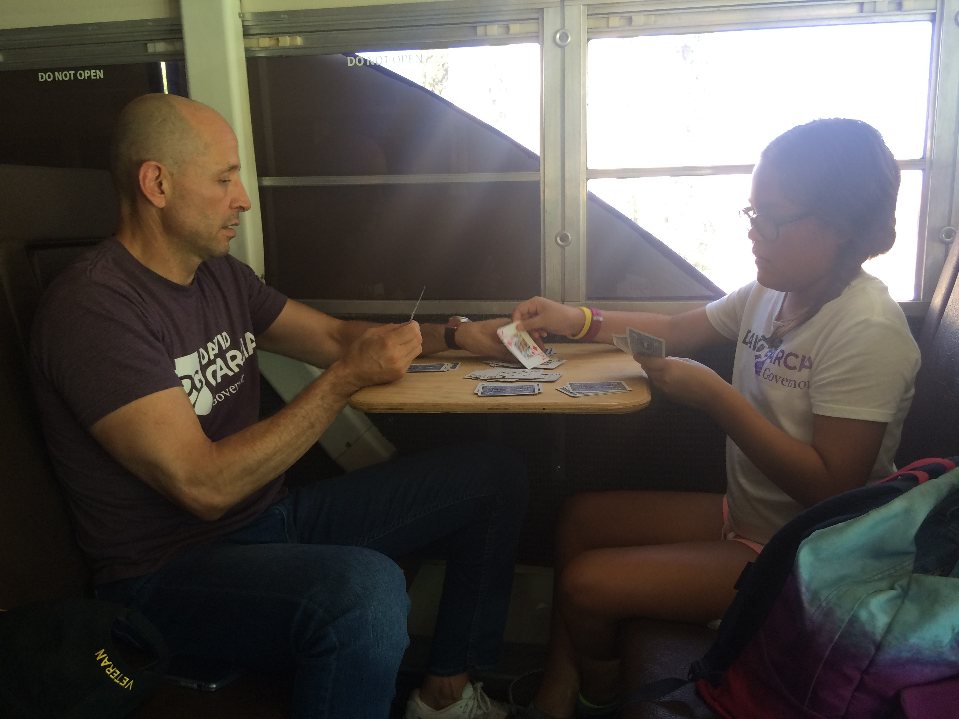 David Garcia, Democratic candidate for Arizona governor, plays speed, a card game, against his daughter Lola on Aug. 19, 2018. The game is often used to pass time during trips in the campaign's converted school bus.