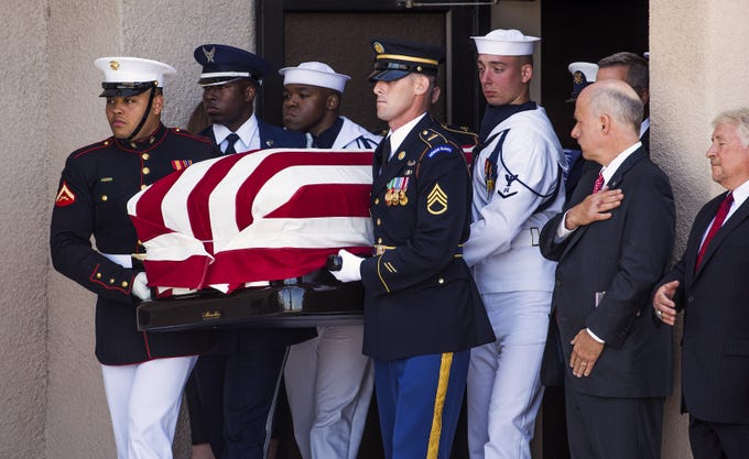 A military honor guard carries the casket of Sen. John McCain from North Phoenix Baptist Church in Phoenix, on Aug. 30, 2018.