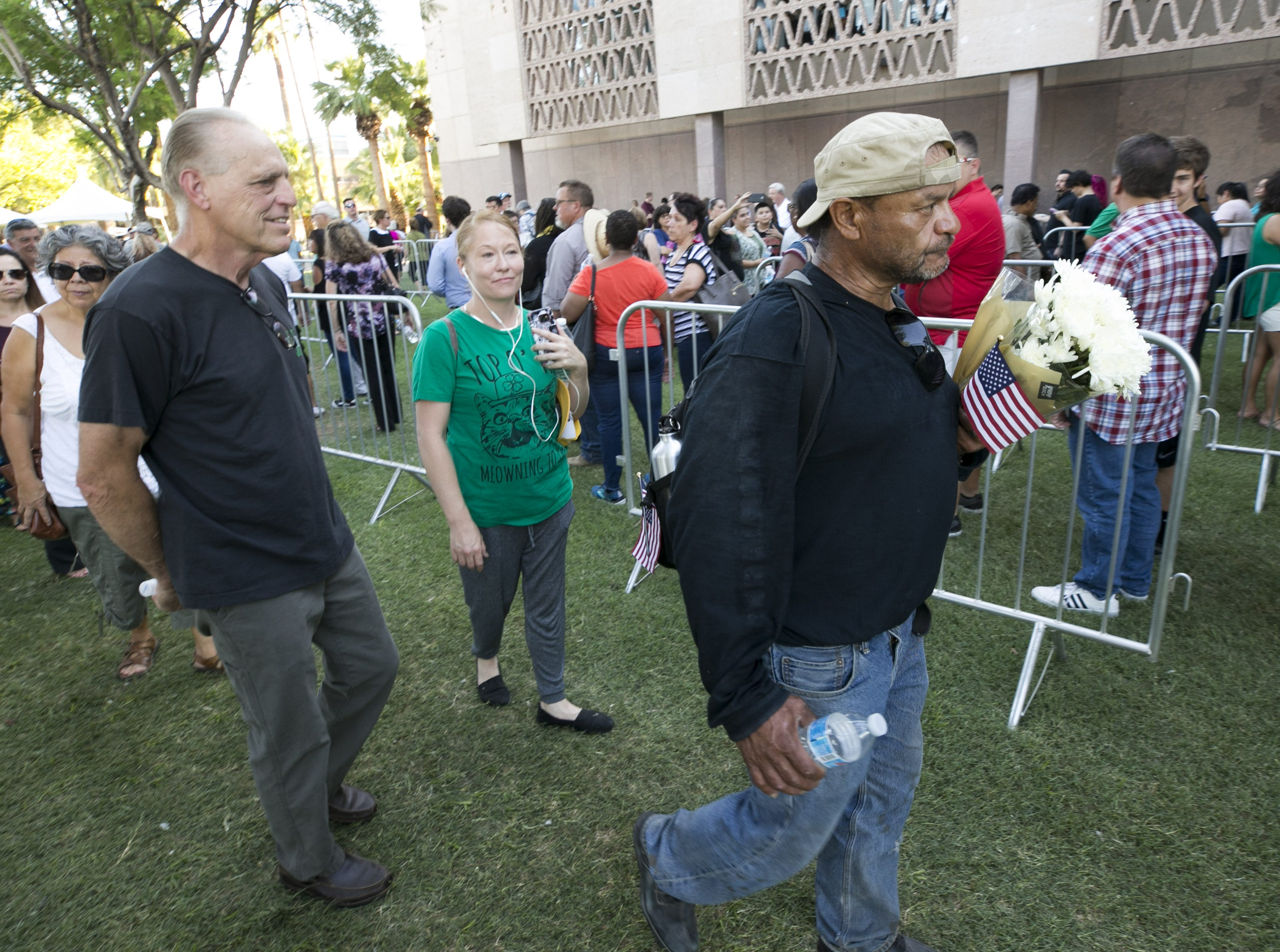 Holding flowers and an American flag, Pedro Montoya of Phoenix, waits in line to pay his respects to Senator John McCain lying in state in the Arizona Capitol in Phoenix on Wednesday, August 29, 2018.