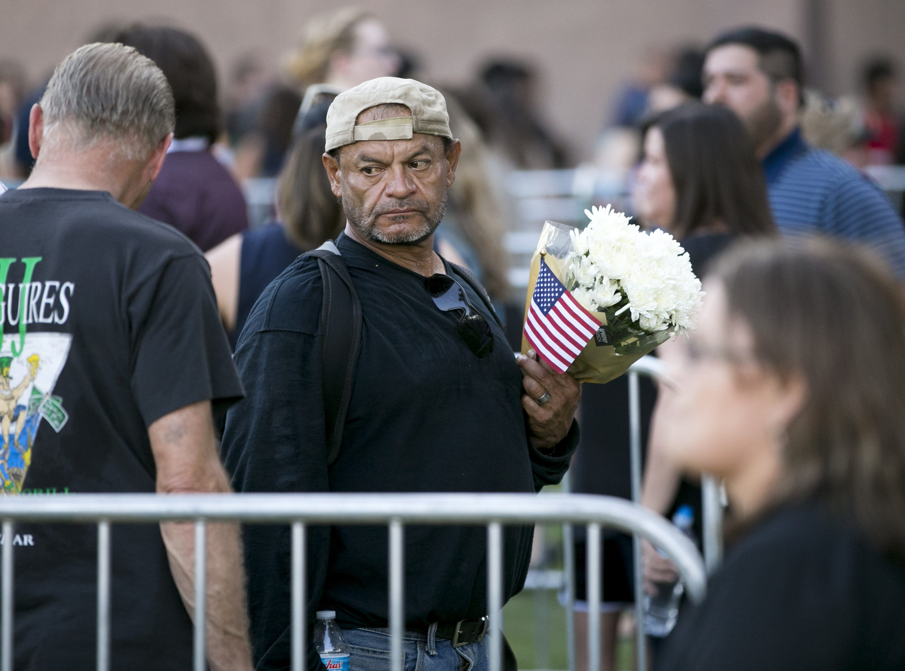 Holding flowers and an American flag, Pedro Montoya of Phoenix waits in line to pay his respects for Senator John McCain lying in state at the Arizona Capitol in Phoenix on Wednesday, August 29, 2018.