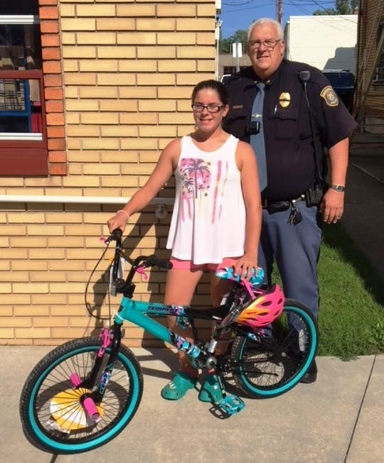 Samantha Tunich won a bicycle in the DARE drawing at the Sanilac County Fair. She is with Croswell Police Chief  Dave Hall