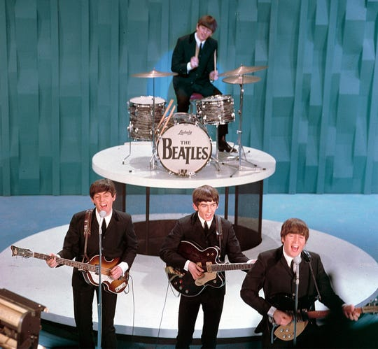 """The Beatles perform on """"The Ed Sullivan Show"""" in New York on February 9, 1964.  From left, front, are Paul McCartney, George Harrison and John Lennon. Ringo Starr plays drums.  (AP Photo)"""