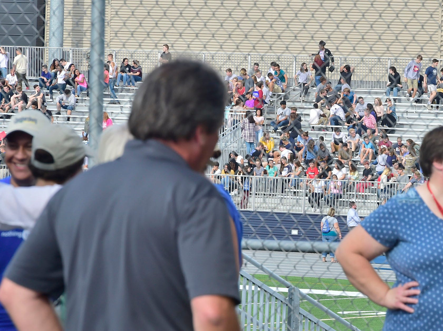 Faculty and students waited in Trojan Stadium after being evacuted. Chambersburg Area Senior High School students were evacuated Thursday morning, August 30, 2018 after a battery ignited a fire in a storage room , sending smoke throughout the building.