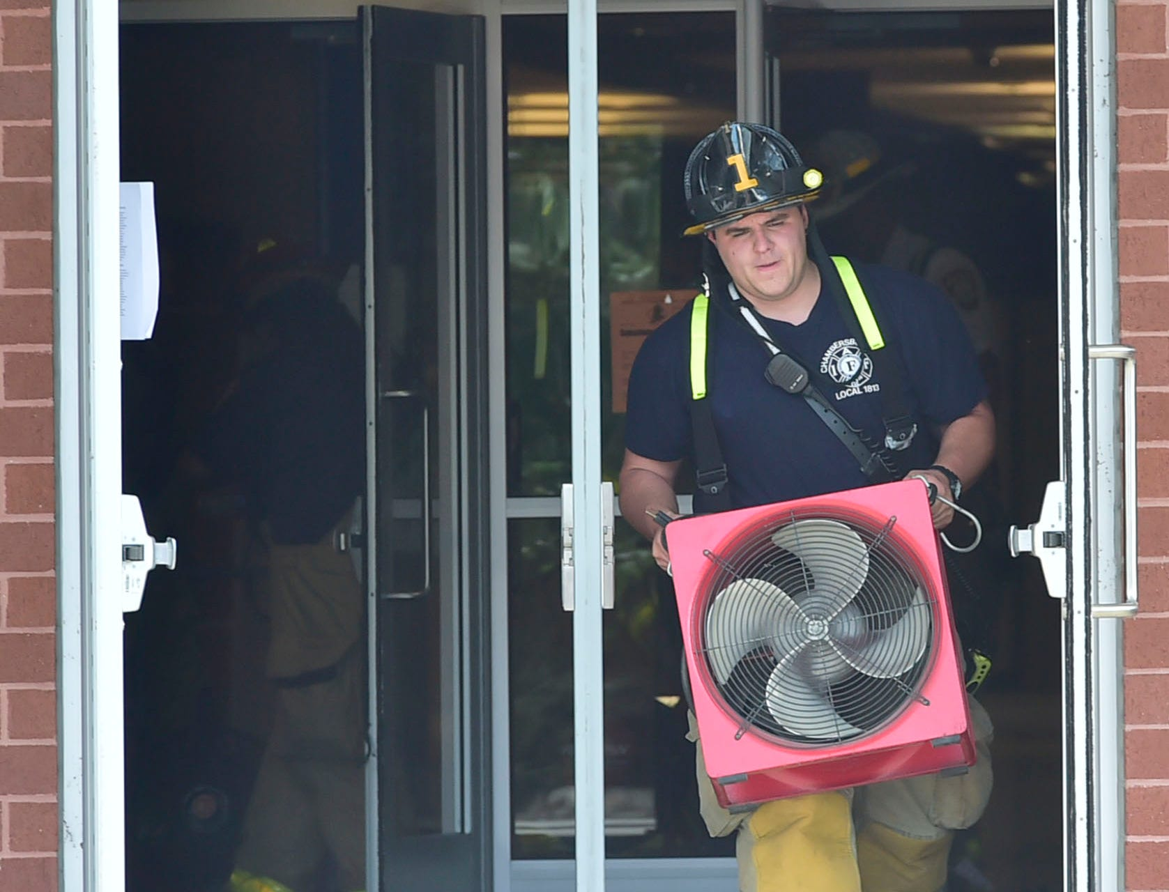A fireman carries a fan from the building. Chambersburg Area Senior High School students were evacuated Thursday morning, August 30, 2018 after a battery ignited a fire in a storage room , sending smoke throughout the building.