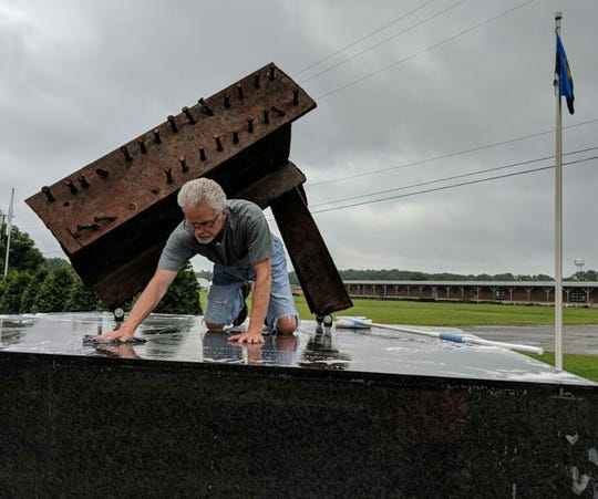 G. Warren Elliott, vice chairman of the 9/11 Memorial Service Committee, spruces up the 9/11 memorial at the Letterkenny Chapel for the annual service on Sept. 9, 2018.