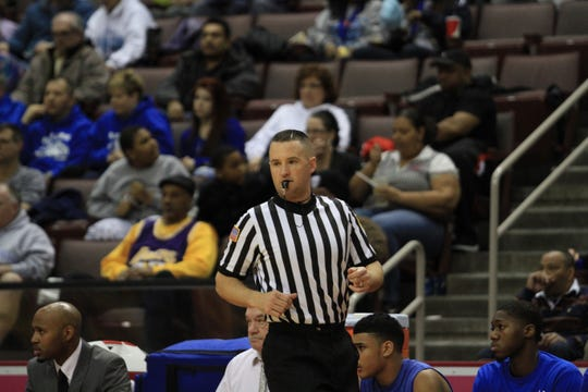 Kevin Lawrence is shown here working as a high school basketball referee.