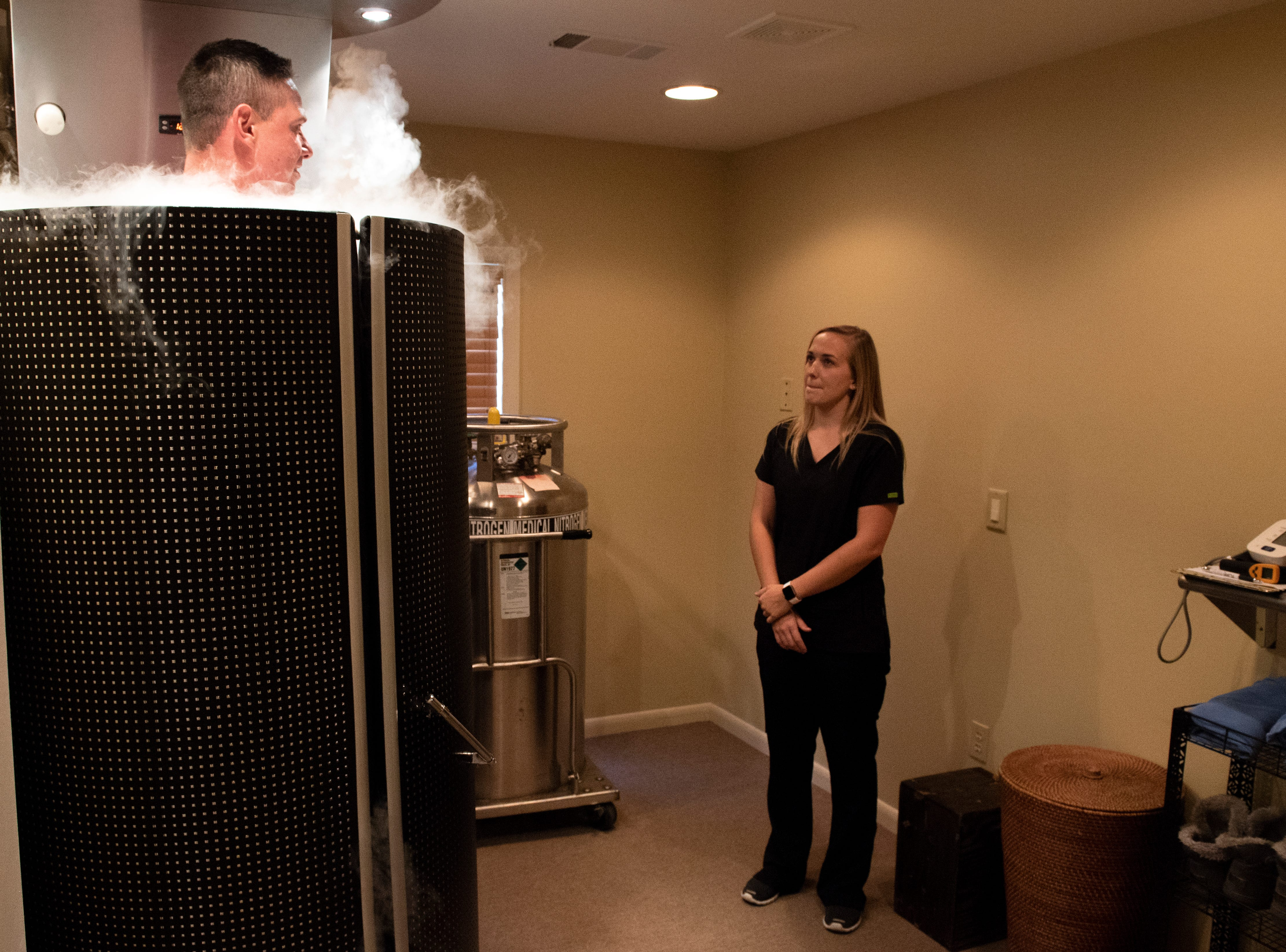 Cryotherapy technician Alison Shreiner, right, speaks with YDR reporter John Buffone while he tries out the cryotherapy chamber, Tuesday, Aug. 27, 2018. Cryotherapy is a treatment using liquid nitrogen gas in an enclosed chamber to surround a patientÕs body with freezing temperatures.