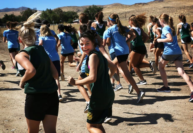 Sparks Middle School student Teresa Miranda, middle, looks back and smiles at her family while competing in a cross country race at Rancho San Rafael Regional Park in Reno on Aug. 30, 2018.