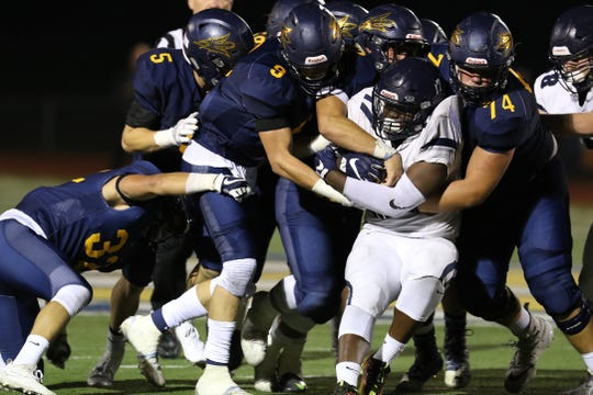 A host of players including Victor's Andrew Russell and CJ Williams (74) try to push Pittsford's Chris Cox back during a 2017 game.