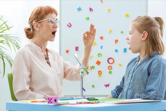 A teacher working on speech with a student.