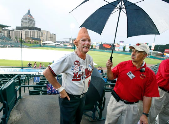 Tom Girot, aka Conehead, tells usher Ken Luciano that he believes the Red Wings game against the Buffalo Bisons will take place after checking the rain conditions at Frontier Field.