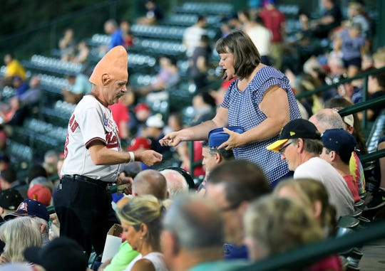 Tom Girot, aka Conehead, gets cash from customer Ann Sojda of Irondequoit for a purchase during a Red Wings game at Frontier Field.