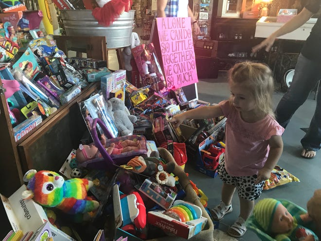 Two-year-old Emma Shaw picks out a new toy during a charity event at Shasta Antique Mall on Wednesday.
