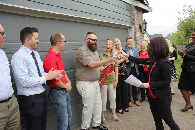 Charlie Patrick (with red key) is handed the key to his new house by Well Fargo Regional Banking District Manager Shea Morrison on Thursday.