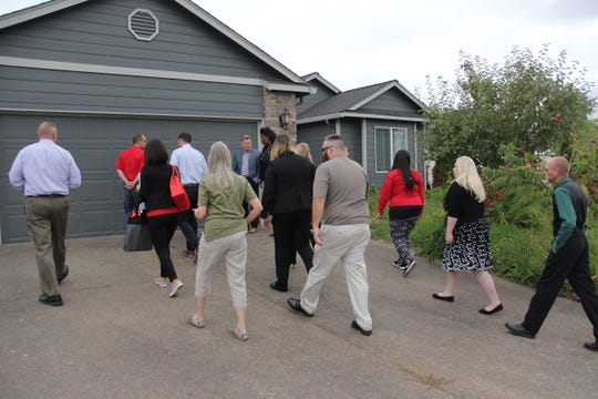 U.S. Army veteran Charlie Patrick (grey shirt, center) follows a group of Wells Fargo employees to his new house for the first time.