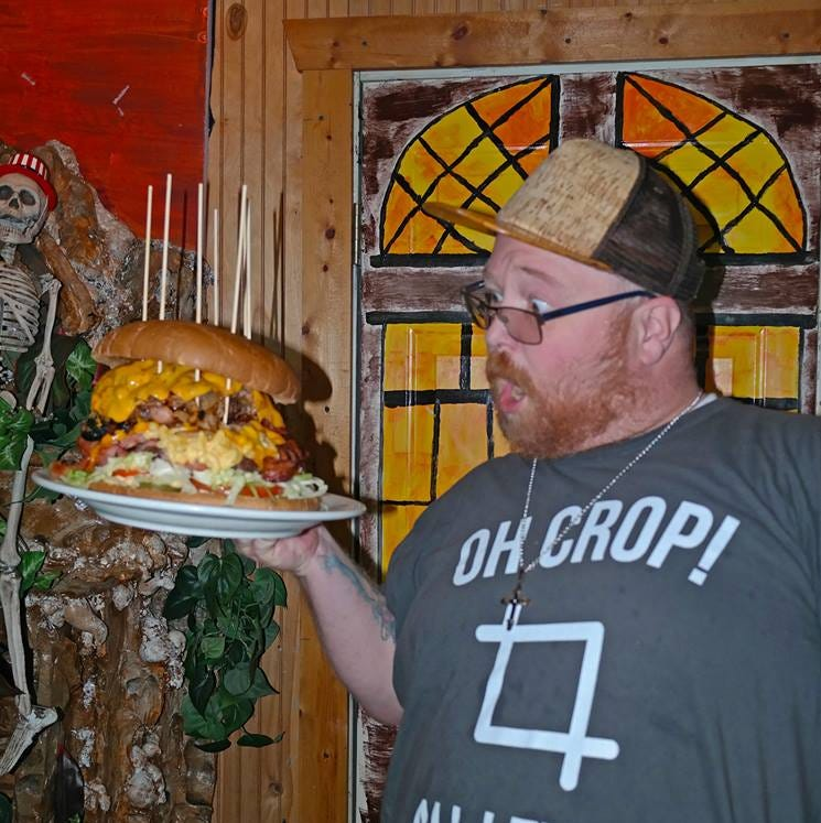 Michael Coschigano holds the Beastie Burger at Whiskers Bar and Grill.  Courtesy of Chuck McMillen Photography.