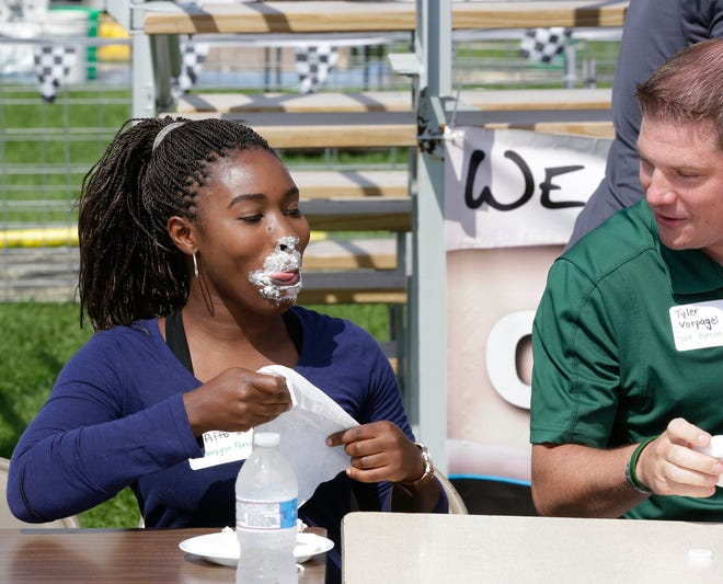 Sheboygan Press' Marina Affo reacts following the cream puff eating contest at the Sheboygan County Fair, Thursday, August 30, 2018, in Plymouth, Wis. At right is Rep. Tyler Vorpagel.