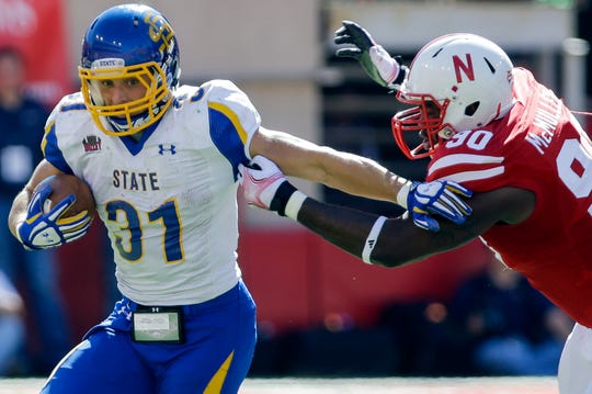South Dakota State running back Zach Zenner (31) runs past the tackle of Nebraska defensive end Greg McMullen (90) in the first half of an NCAA college football game in Lincoln, Neb., Saturday, Sept. 21, 2013. (AP Photo/Nati Harnik)