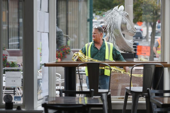 City of Sioux Falls street department Charlie Putzier gathers caution tape in front Coffea Roasterie Thursday, Aug 30, in downtown Sioux Falls. A facade is leaning and will likely need to be replaced.
