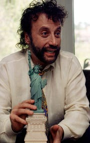In this June 7, 2001 photo, comedian Yakov Smirnoff talks about his past 15 years as a U.S. citizen during an interview at his Branson theater. Smirnoff is holding the replica of the Statue of Liberty that he held when he was sworn in as a naturalized citizen on July 4, 1986. (AP Photo/John S. Stewart)