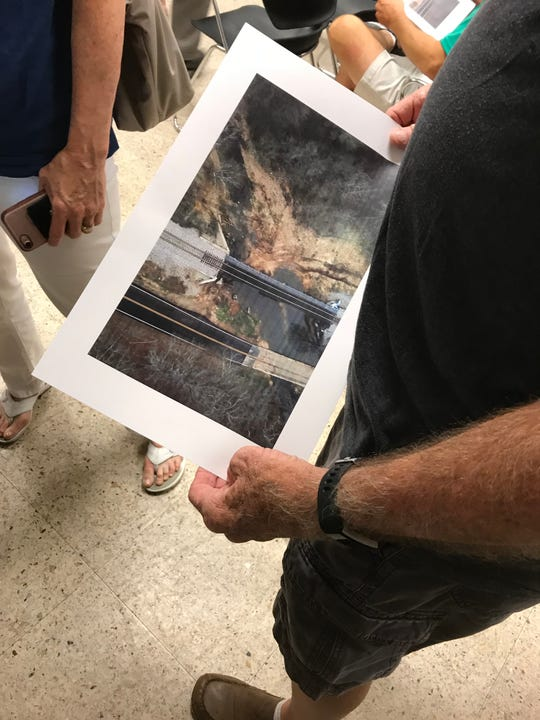 A man looks at an aerial photo of the railroad tracks which run along Farm Road 193, east of Springfield.