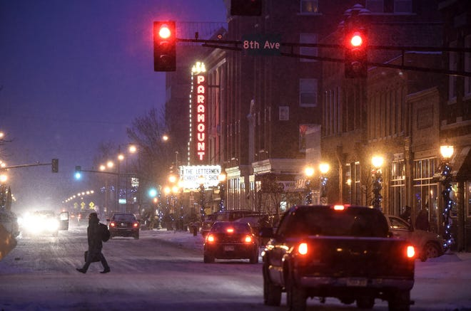 A pedestrian crosses St. Germain Street in downtown St. Cloud on a chilly evening in 2017.