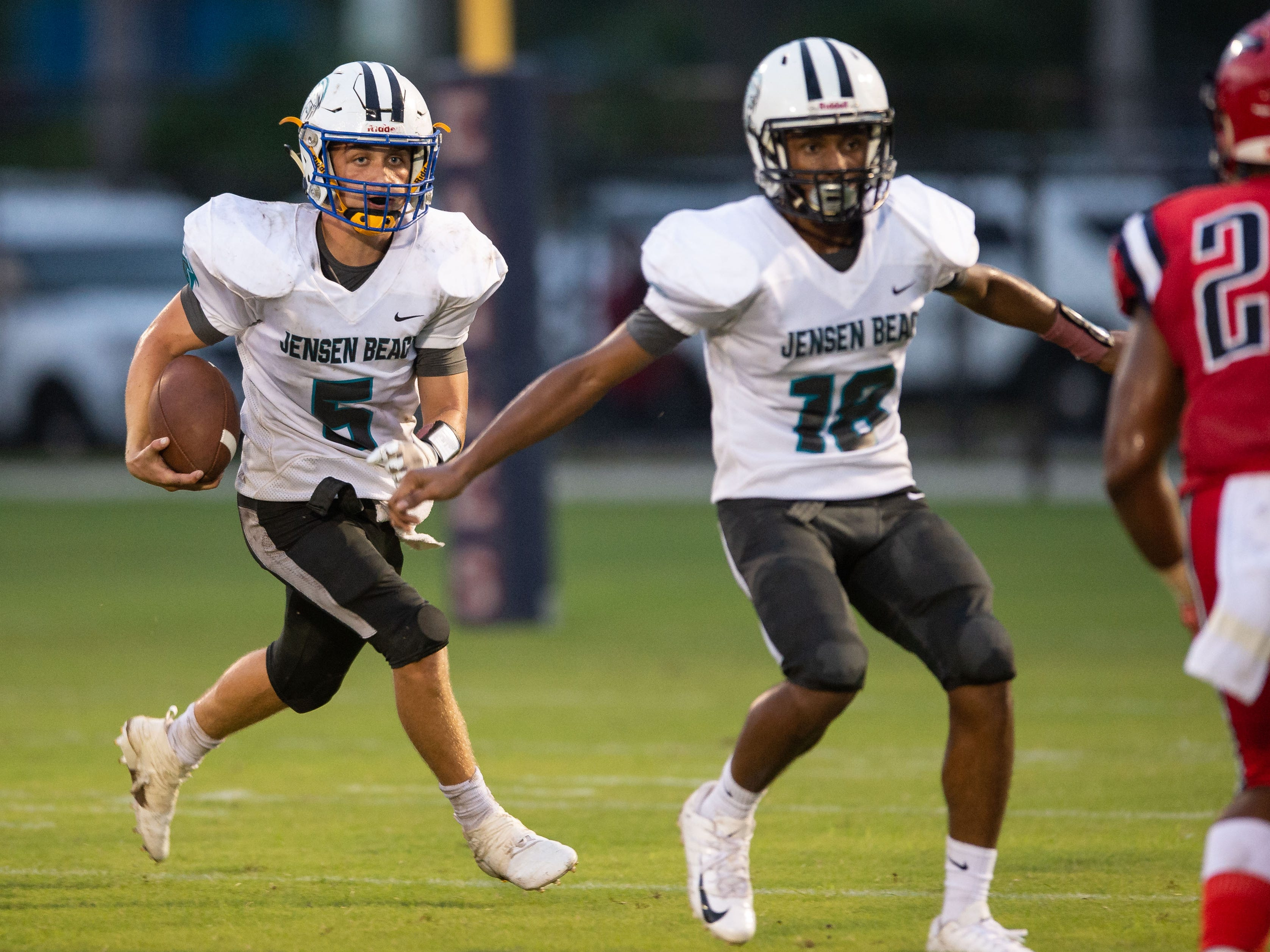 Jensen Beach quarterback Bradyn Bytheway (left) runs the ball near the end of the first half, as teammate Da'Quan Gonzales prepares to block St. Lucie West Centennial's Ja'Darius Sanders, during the high school football game Wednesday, Aug. 29, 2018, at South County Regional Stadium in Port St. Lucie.