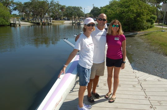 """Friends After Diagnosis Founder and Facilitator Lin Reading, Vero Beach Rowing Director Austin Work and Indian River Impact 100 Grants Chair Brenda Cetrullo  at the christening of the new rowing shell, """"Friends."""""""