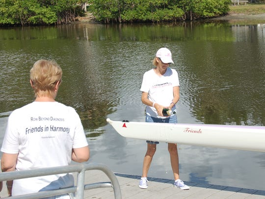 """Lin Reading, Friends After Diagnosis founder and facilitator, pours champagne on the bow of the """"Friends"""" rowing shell at the MacWilliam Park Boat Basin."""