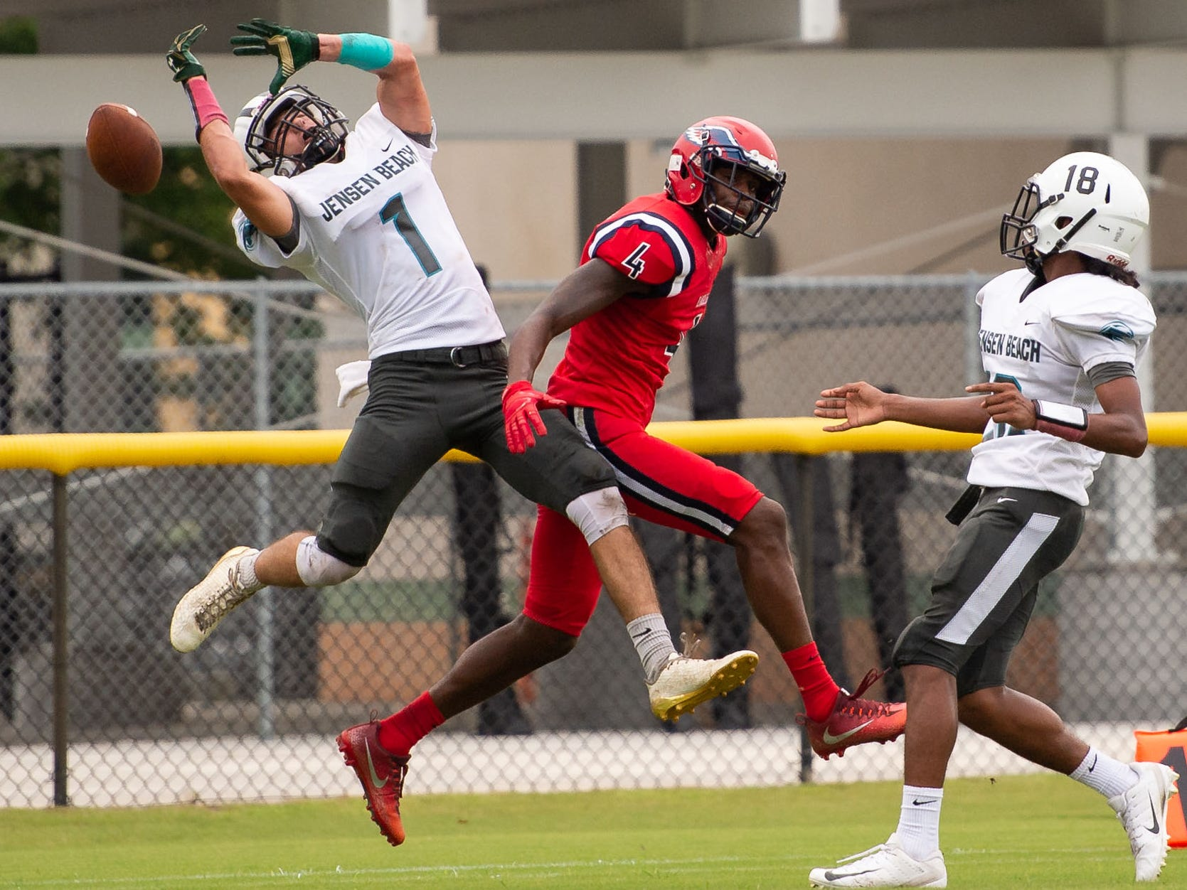 Jensen Beach's Liam Zaccheo (right) nearly intercepts a pass intended for St. Lucie West Centennial's Trequan Collins in the first quarter of the high school football game Wednesday, Aug. 29, 2018, at South County Regional Stadium in Port St. Lucie.