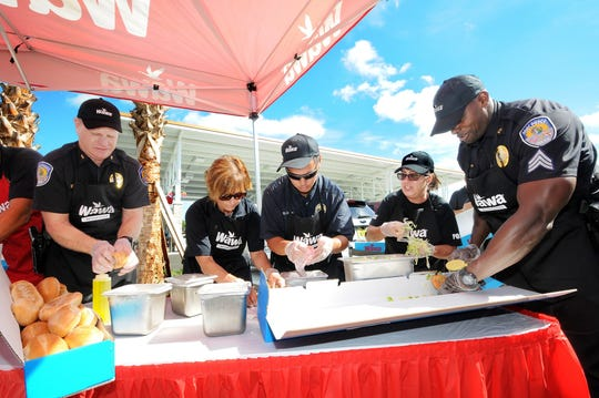 The Fort Pierce Police Department Hoagie Making Team consisted of, from left, Acting Deputy Chief Robert Ridle, Sergeant Christine Davis, Crime Prevention Officer Damian Spotts, Detective Ludmila Quintao, and Sergeant Willis Tumblin. Their assembly line worked like a well-oil machine to produce 19 hoagies, made the WAWA way, to clinch the victory over the St. Lucie County Fire District.