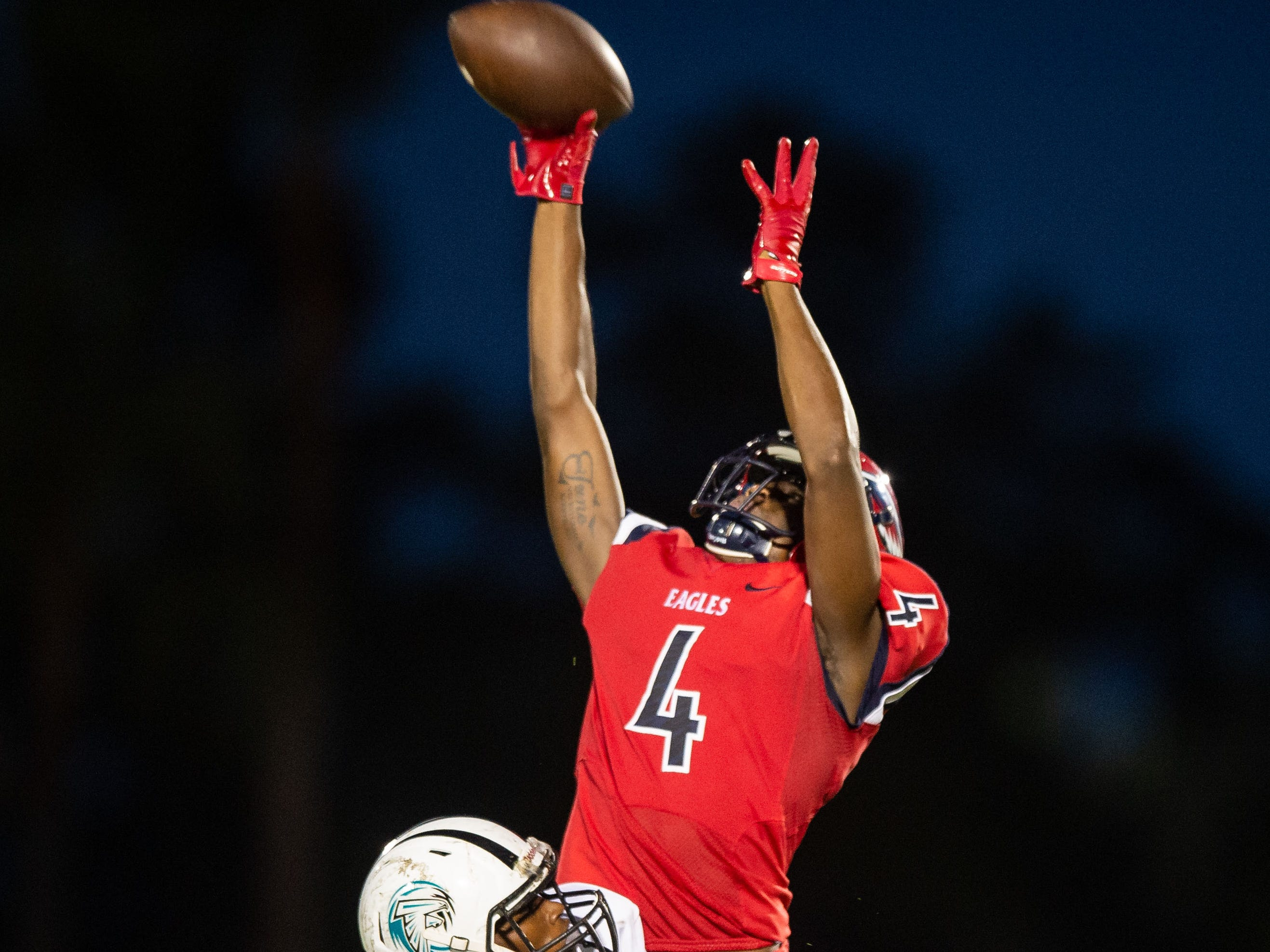 St. Lucie West Centennial's Trequan Collins leaps to catch the ball, then runs downfield into scoring position, as Jensen Beach's Terrence Wilson defends in the third quarter of the high school football game Wednesday, Aug. 29, 2018, at South County Regional Stadium in Port St. Lucie.
