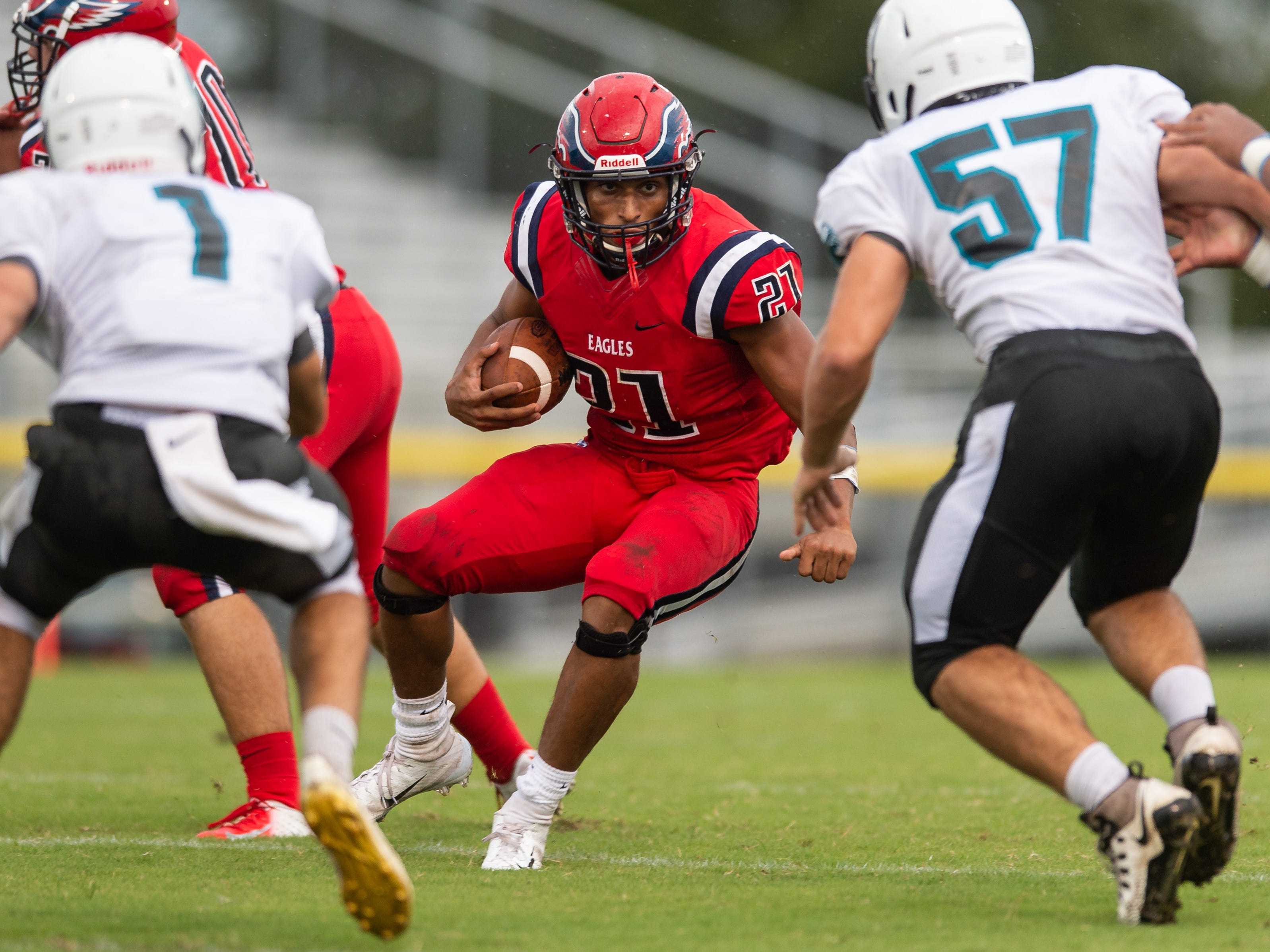 St. Lucie West Centennial's Cedrick Wilcox (center) stares down Jensen Beach defender Andrew Perry (right) on a run in the second quarter of the high school football game Wednesday, Aug. 29, 2018, at South County Regional Stadium in Port St. Lucie.