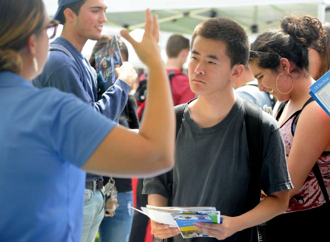 Justin Tsang, of Moorpark, talks with Brennan Burnett, a senior assistant director at UCLA during Transfer Day on Thursday at Moorpark College. The event is designed to encourage students to attend four-year universities when they finish community college.