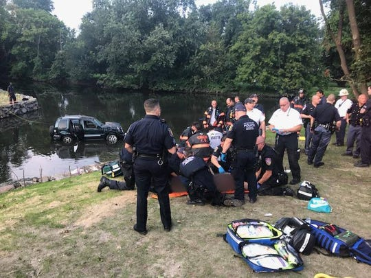 First-responders at the scene of a car crash that occurred where the Bronx River Parkway and Sprain Brook Parkway split, leaving one vehicle in the water.