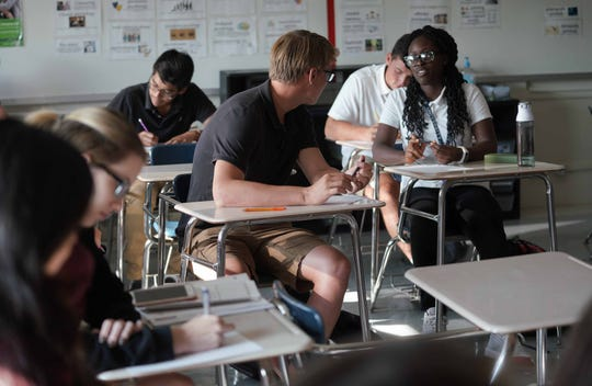Ryan Pirrung, 17, a senior at Conrad School of Science, talks with his new classmate Aissata Diallo, in his AP Psych class while taking part in an exercise to learn new things about fellow classmates on the first day of school.