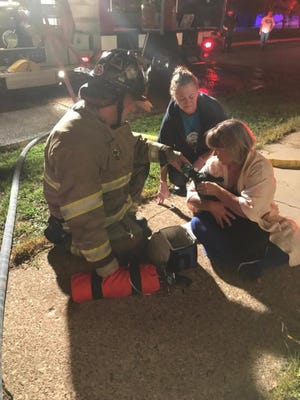 A Wisconsin Rapids firefighter gives oxygen to a dog that was caught in a house fire Thursday, August 30, 2018.