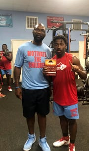 "Nick Moore, a former Division I player from Wichita Falls (Rider) at Arizona State, poses with the top 2018 Wichita Falls area recruit, Daimarqua Foster of Hirschi, holding up Moore's new book, ""Never Too Late."""
