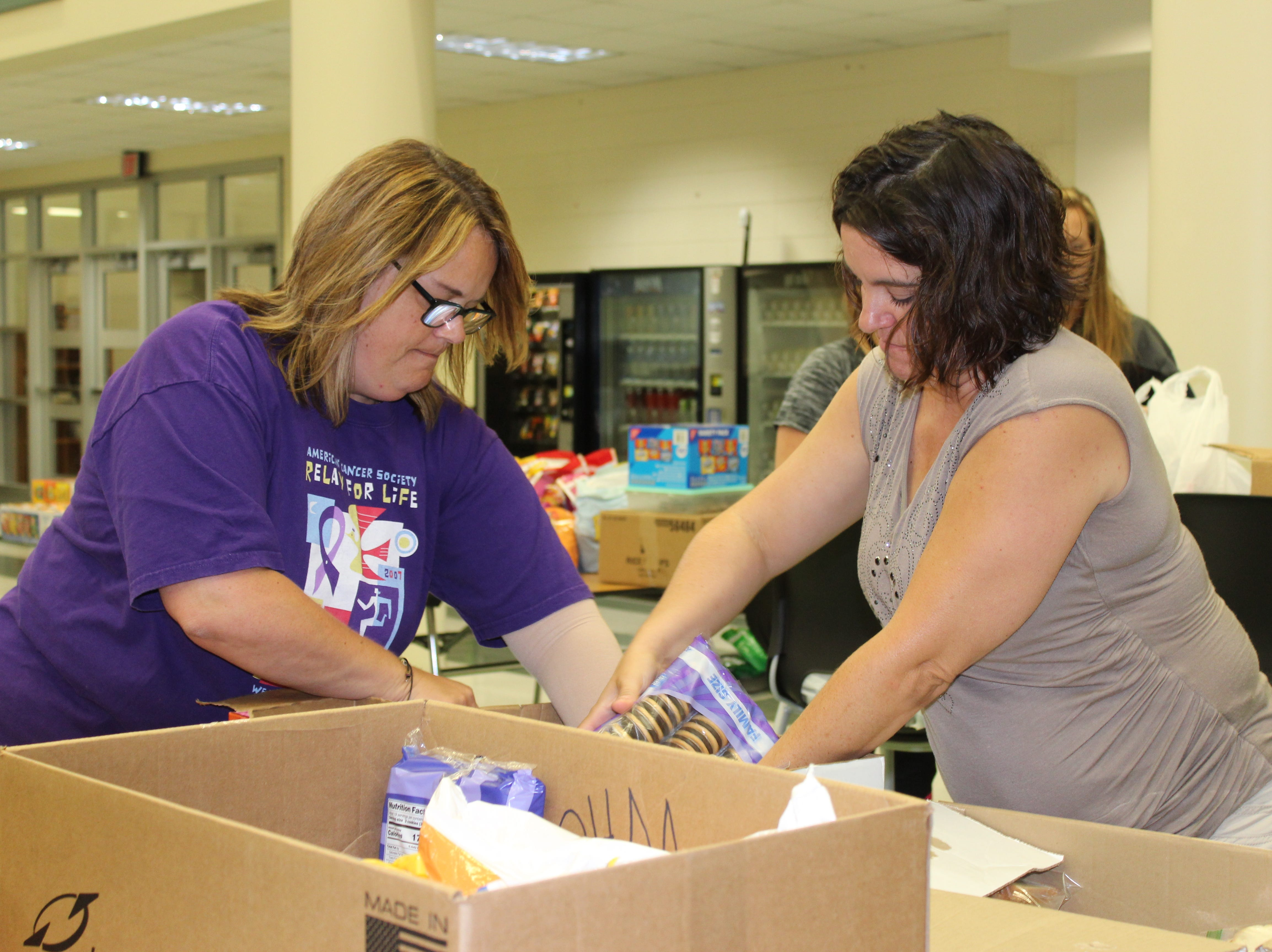 Staff members at Waupun Area High School fill boxes with food to be taken out to work sites.