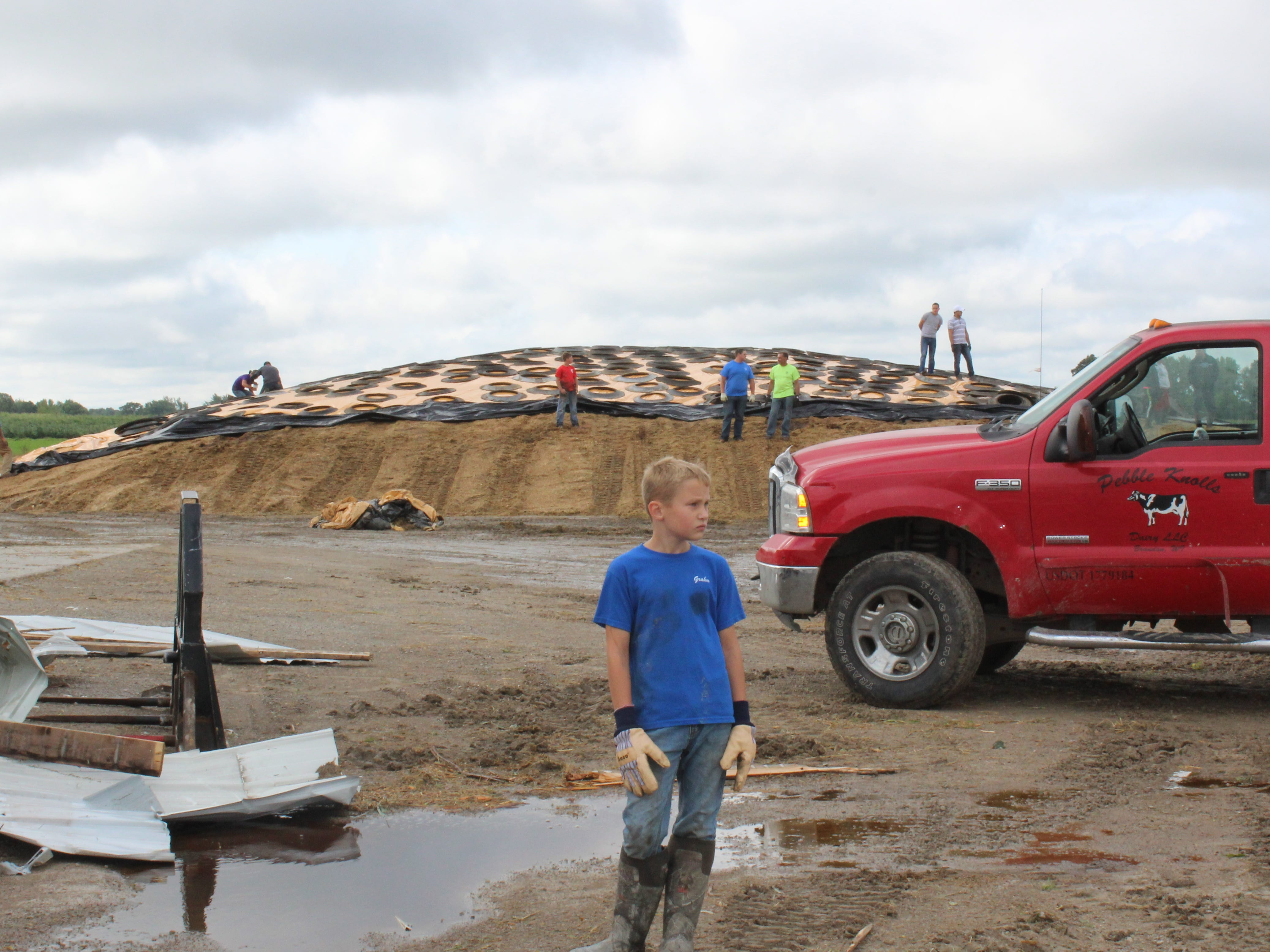 Volunteers from area businesses, farms, schools help cover a feed pile at Pebble Knolls Dairy near Alto.