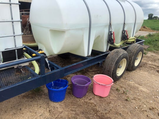 With no electricity to power pumps, a water transfer tank is used to water heifers at two different locations at Lyn-Vale Holsteins in Sheboygan County after severe storms moved through on Aug. 28.