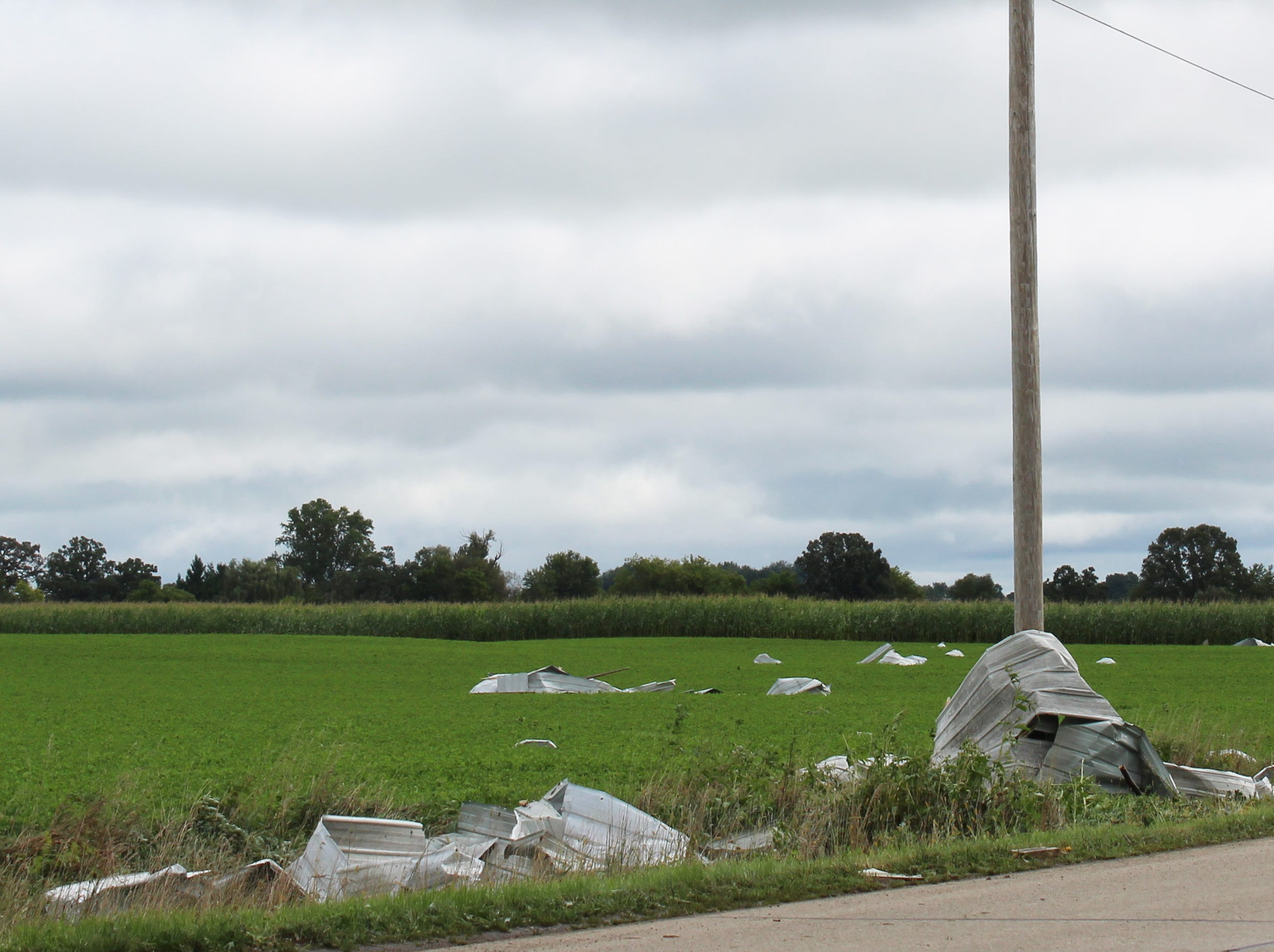 Sheet metal is seen scattered in a nearby farm field. Volunteers will later walk the fields to search for metal that may ruin equipment or injure cows.