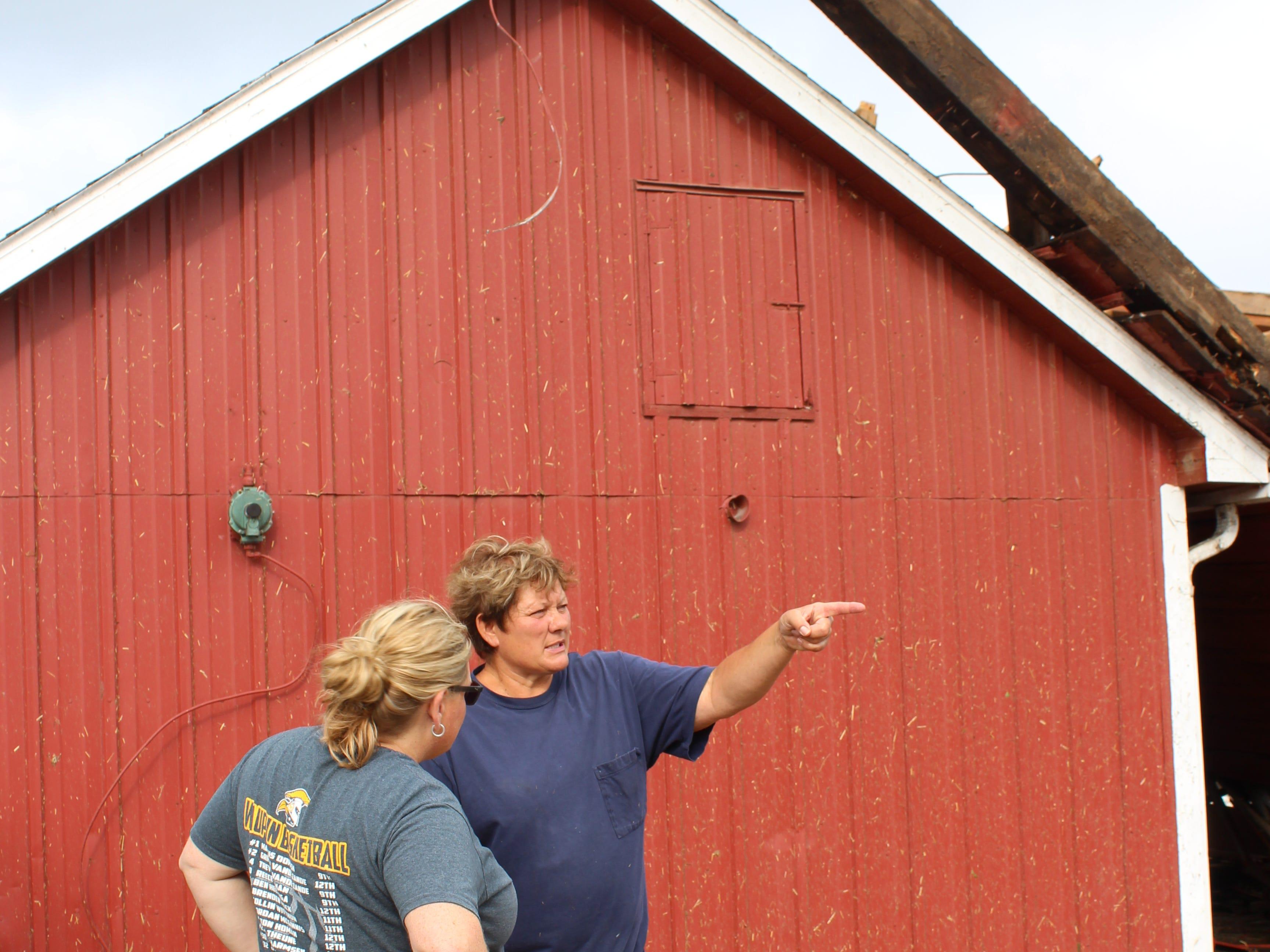 Robyn Pluim (right) shows volunteer Jen Schramm the damage on her Waupun area farm.