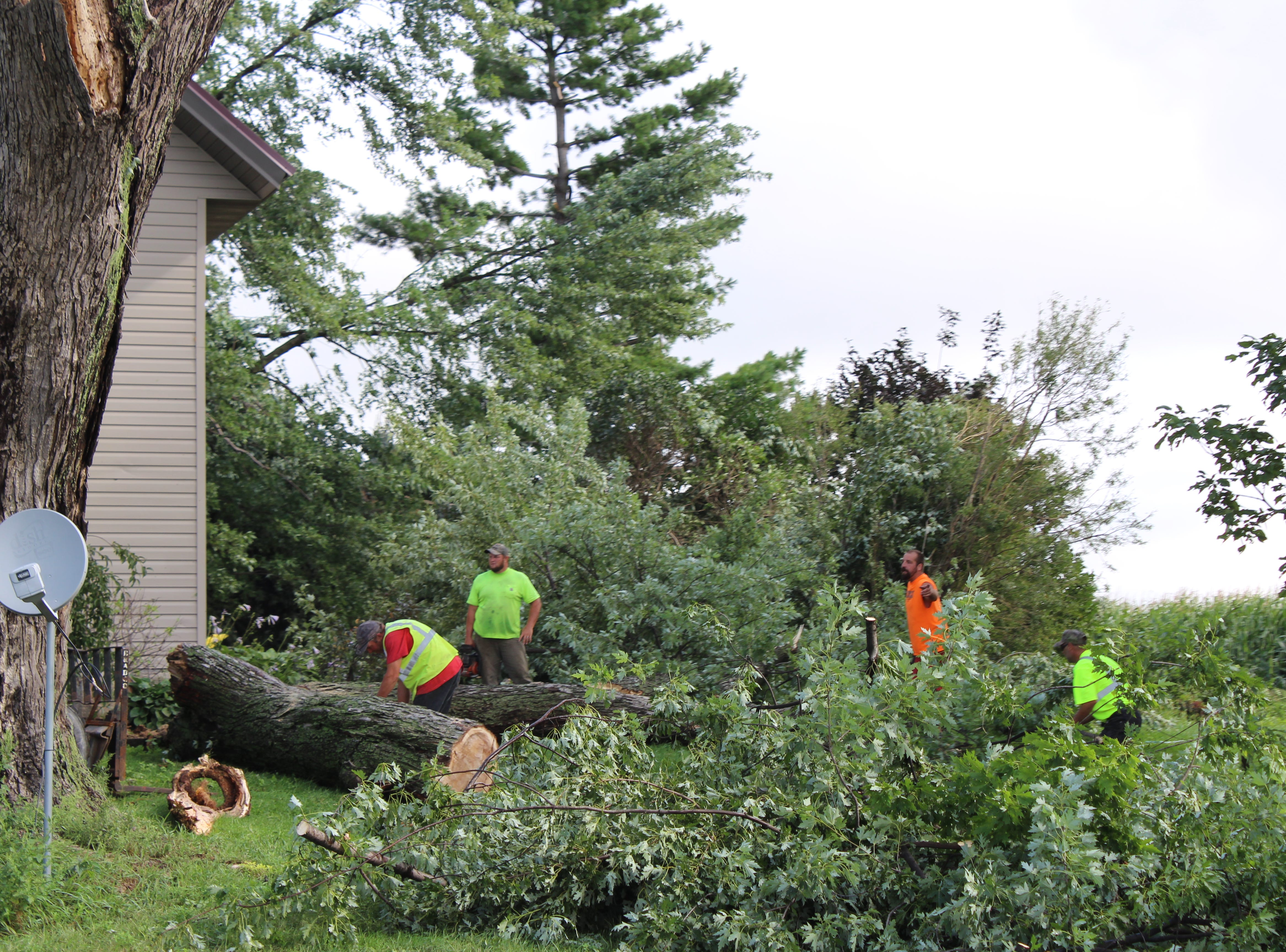 Volunteers cut up downed trees on the front lawn of Eric and Danielle Wetzel's home on Hemp Road.