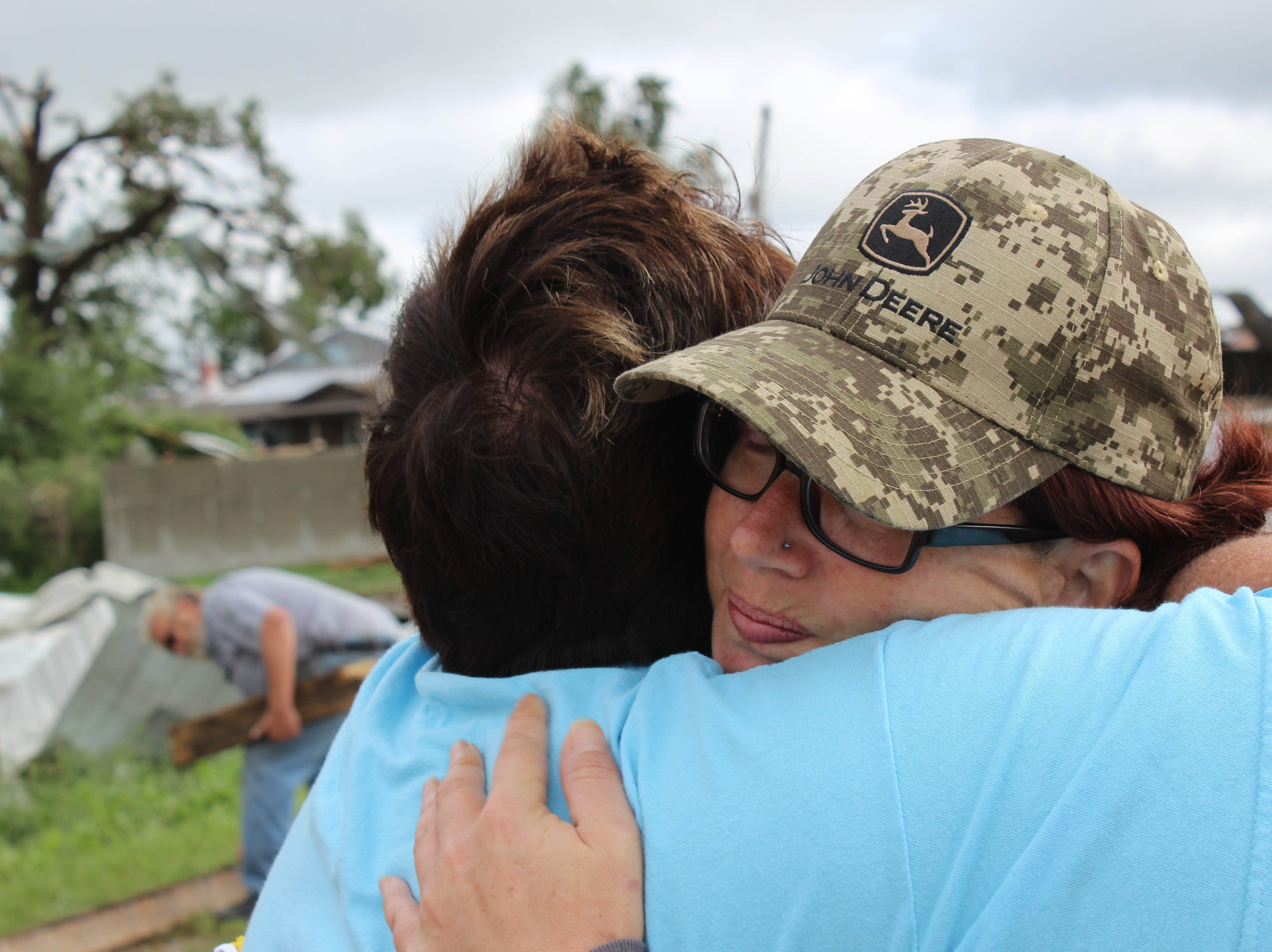 Waupun Agriculture teacher and FFA advisor Tari Costello (left) gives Danielle Wetzel a hug and some moral support as the Wetzel family copes with wide spread destruction on their family farm east of Alto.