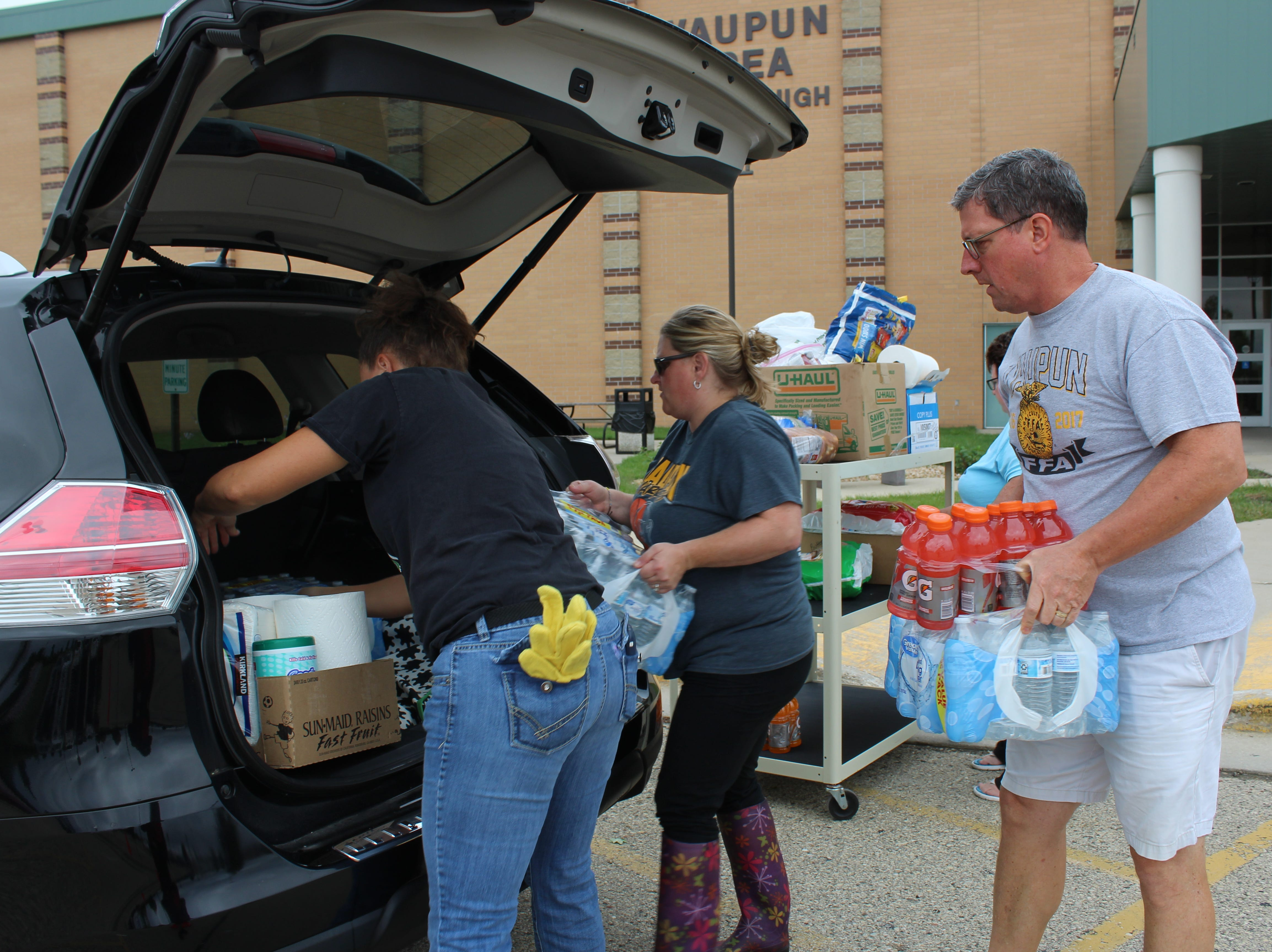 Waupun Area School District staff members load supplies and food into a vehicle to be delivered to sites impacted by the July 28 tornado.