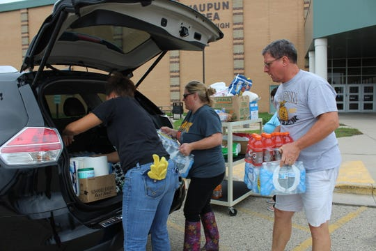 Waupun Area School District staff members load supplies and food into a vehicle to be delivered to sites impacted by the Aug. 28 tornado.