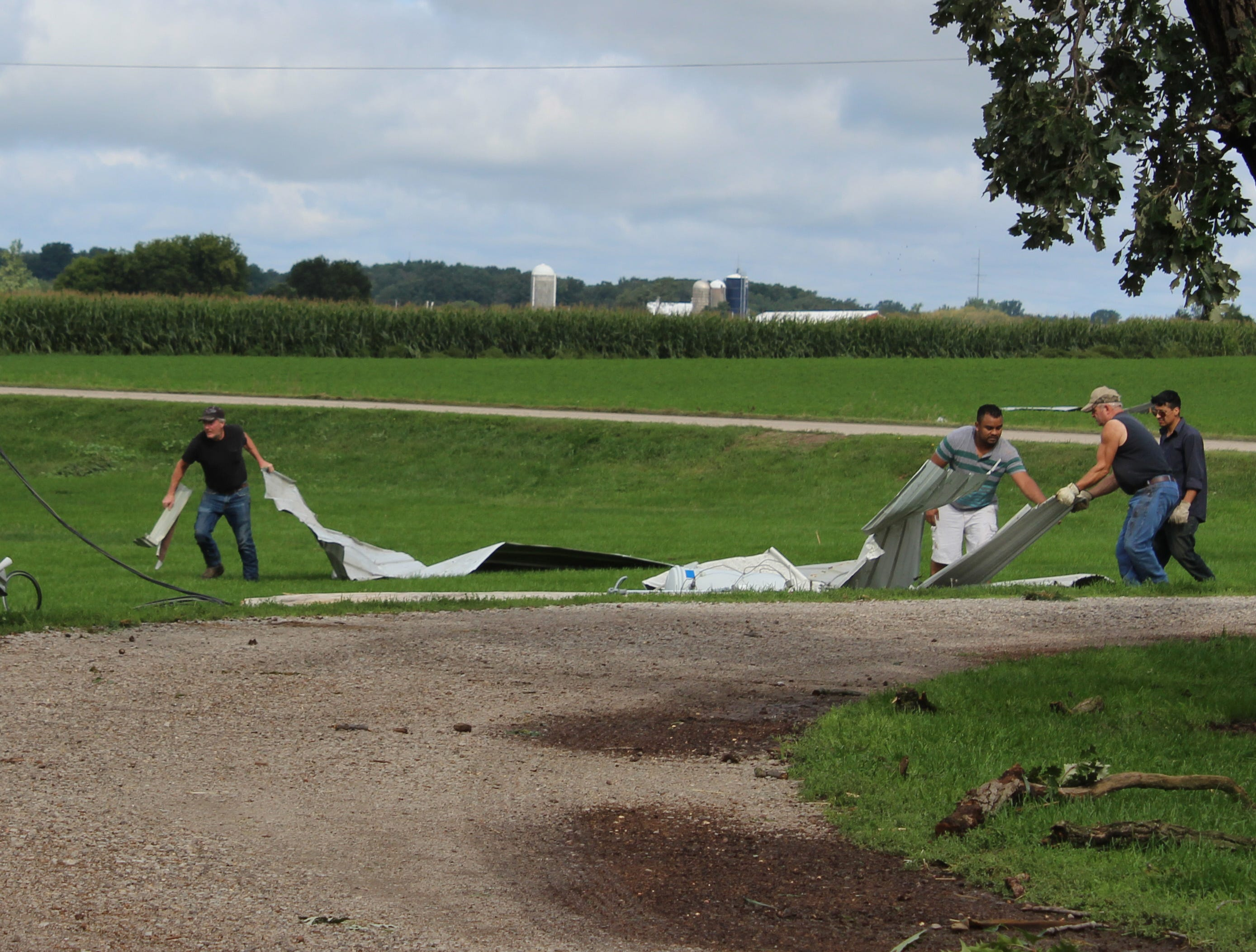 Volunteers collect sheet metal that was strewn around the farm by a tornado.
