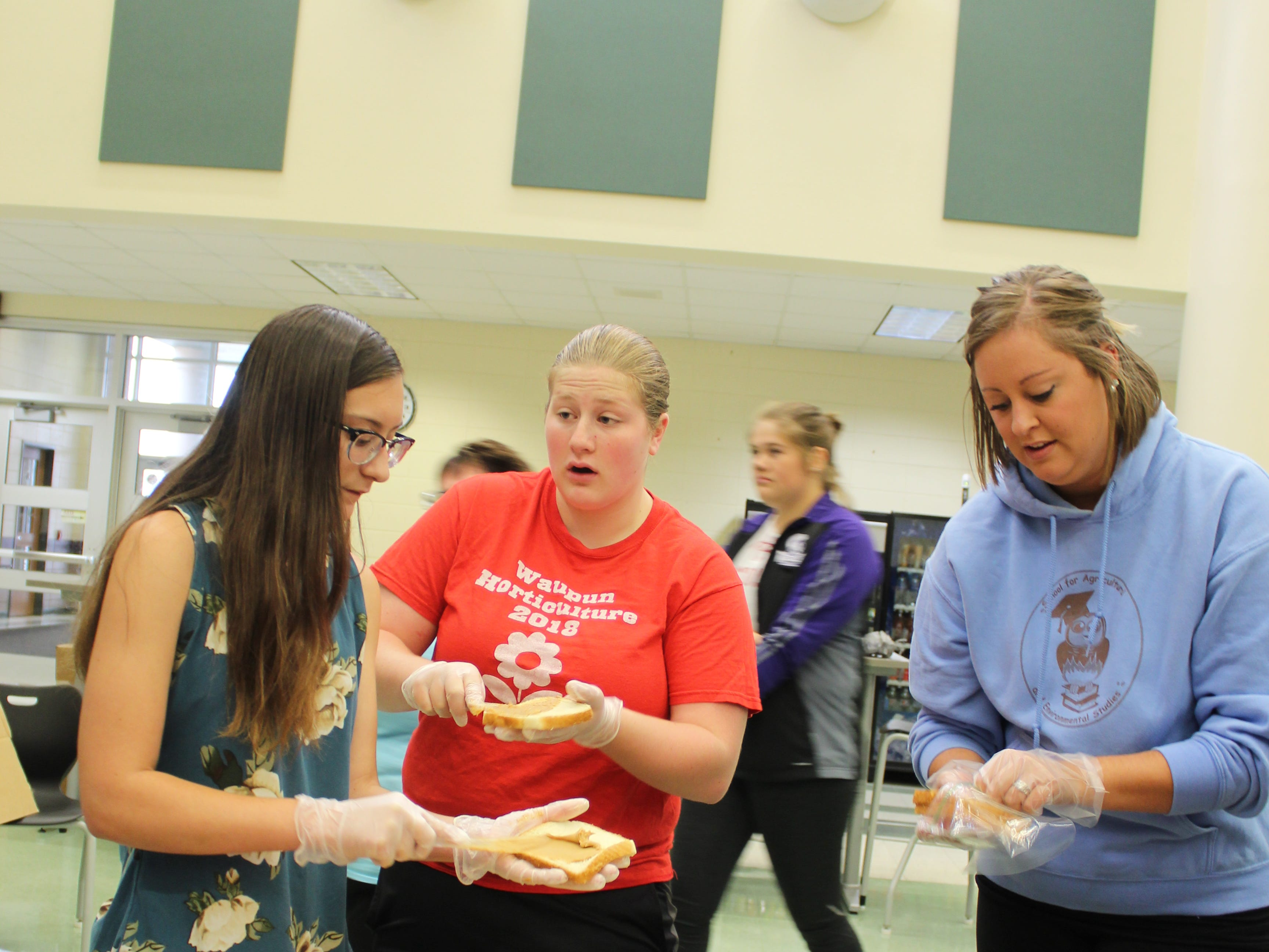 Waupun FFA members (from left) Sam Horning, Alexa Kuhn and Kelli Bonack make sandwiches for volunteers and utility workers cleaning up and repairing damage in the wake of the July 28 storm.