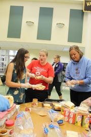 Waupun FFA members (from left) Sam Horning, Alexa Kuhn and Kelli Bonack make sandwiches for volunteers and utility workers cleaning up and repairing damage in the wake of the Aug. 28 storm.